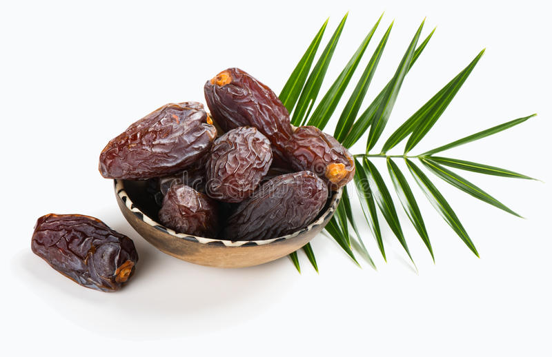 Dates fruifs Medjool. Medjool dates in a bowl and green leaf isolated on white background stock image