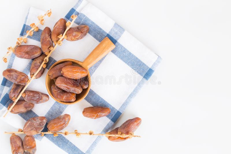 Dates fruit in wooden ladle on white background,Dried date palm. Fruits top view stock photo