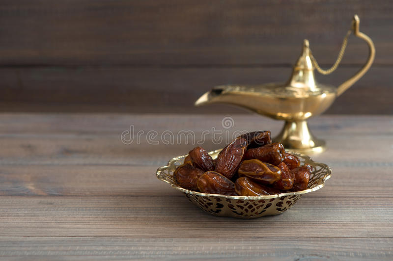 Dates in golden bowl and arabian lamp stock images