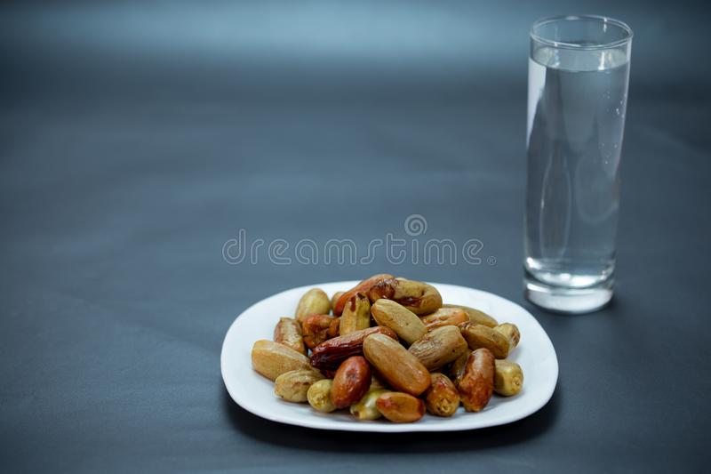 Nigeria local dates with glass of water on black background stock image