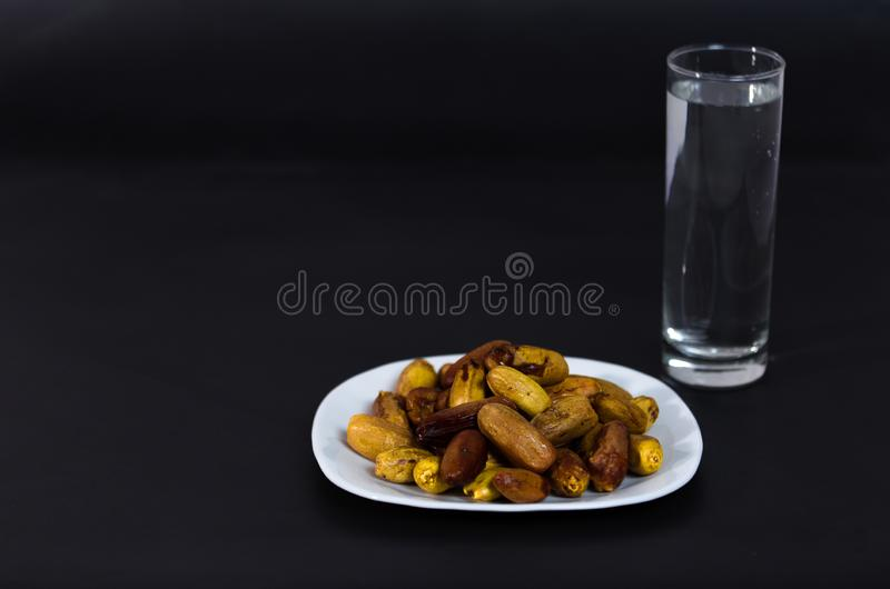 Nigeria local dates with glass of water on black background stock photo
