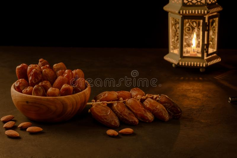 Dates in wooden bowl and lantern on stone table. Muslim holy month Ramadan Kareem. Copy space stock photos