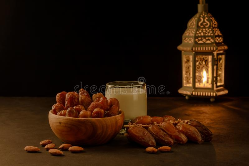 Dates in wooden bowl, milk and lantern on stone table. Muslim holy month Ramadan Kareem. Copy space royalty free stock photos
