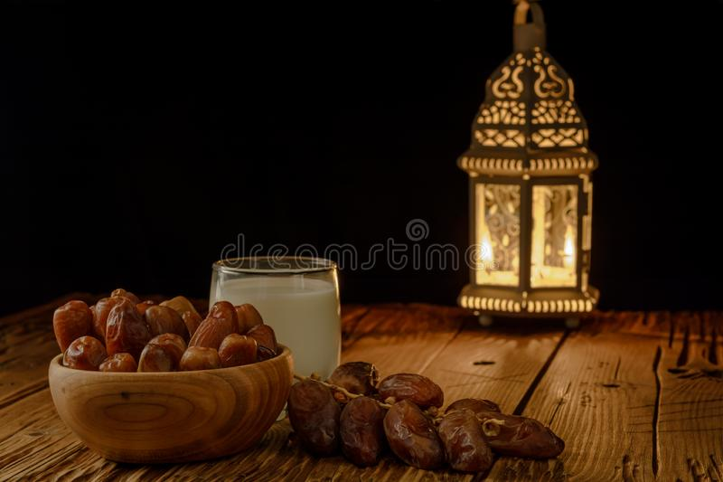Dates in wooden bowl, milk and lantern on wooden table. Muslim holy month Ramadan Kareem. Copy space royalty free stock photography