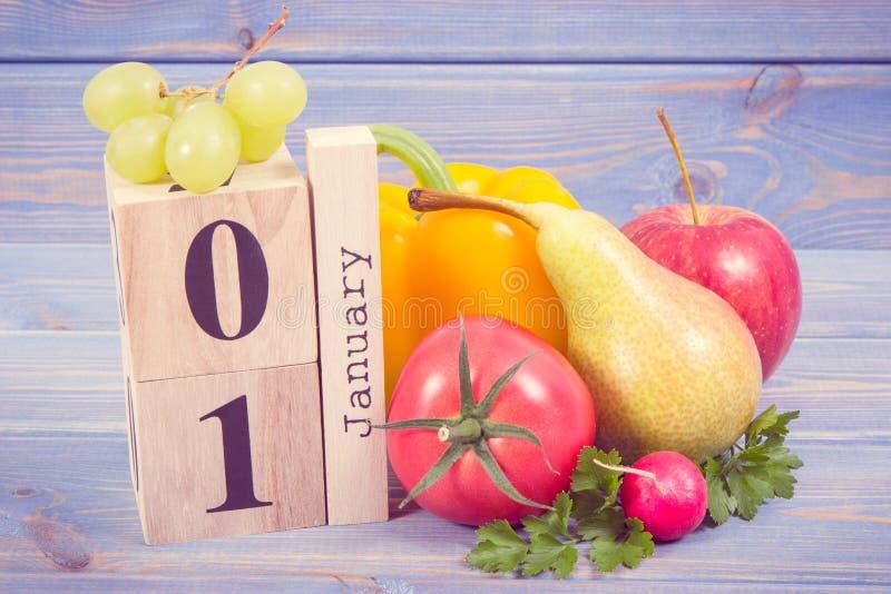 Dati il 1° gennaio sul calendario del cubo e la frutta fresca con le verdure, concetto delle risoluzioni dei nuovi anni di nutriz fotografie stock libere da diritti
