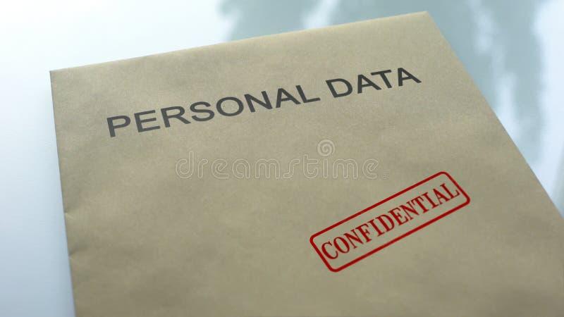 Dati personali confidenziali, guarnizione timbrata sulla cartella con i documenti importanti immagini stock libere da diritti