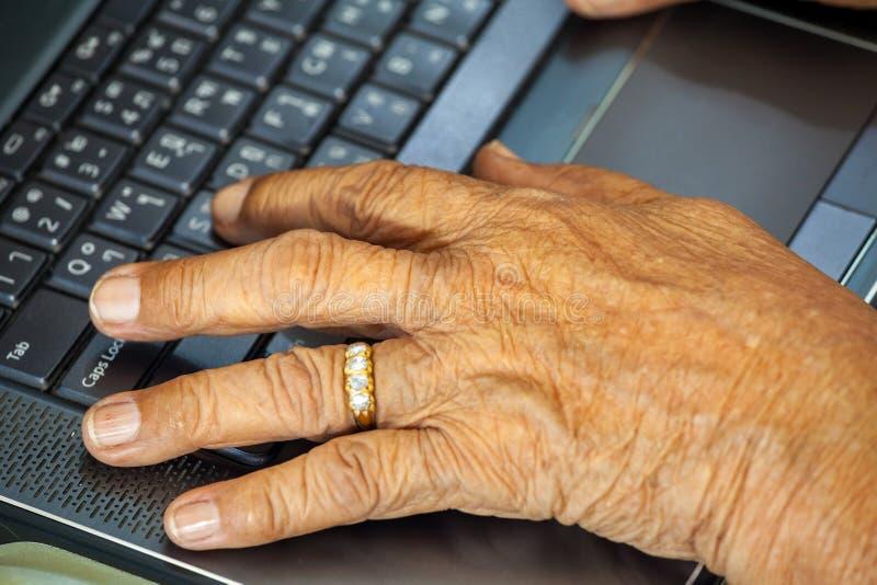 Datilografia das mãos da pessoa idosa imagem de stock