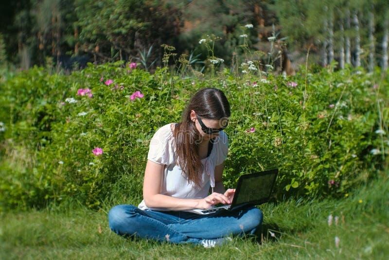 Datilografia de trabalho da menina moreno bonita no portátil que senta-se no parque no verão foto de stock royalty free
