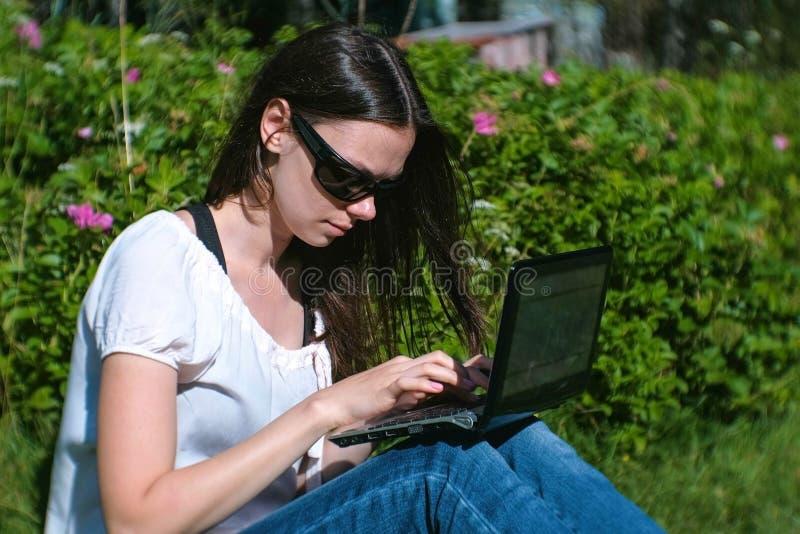 Datilografia de trabalho da menina moreno bonita no portátil que senta-se no parque no verão foto de stock