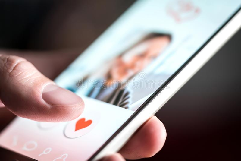 Dating app or site in mobile phone screen. Man swiping and liking profiles. Dating app or site in mobile phone screen. Man swiping and liking profiles on stock photo
