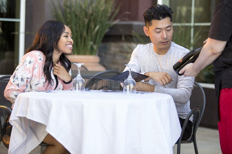 Dating Couple Ordering at an Outdoor Restaurant. Interracial couple on a date ordering from a waiter in an outdoor restaurant. The customers are looking at a stock images
