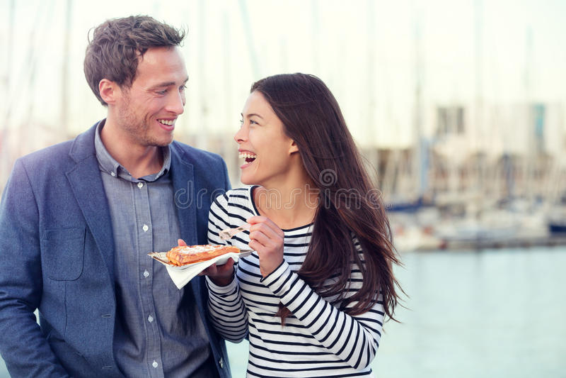 Dating couple tourists eating waffles on date. Enjoying food snack. Romantic men and women laughing having fun outdoors. Multiracial couple, Young Caucasian men stock image
