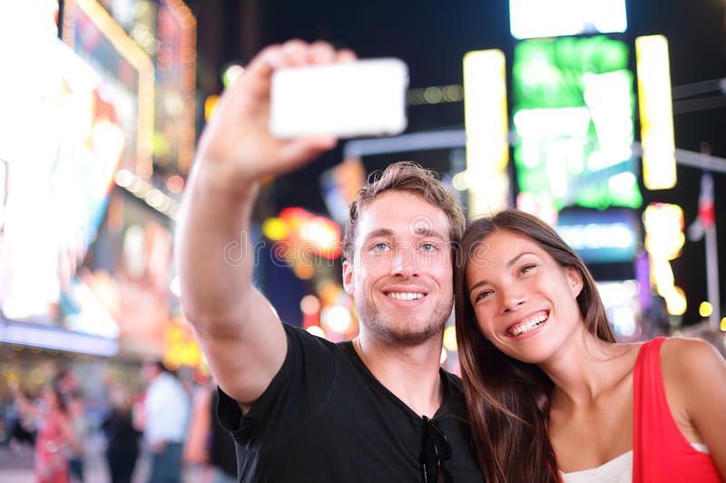 Dating young couple happy in love taking selfie photo on Times Square, New York City at night. Beautiful young multiracial tourist. Dating young couple happy in royalty free stock photos