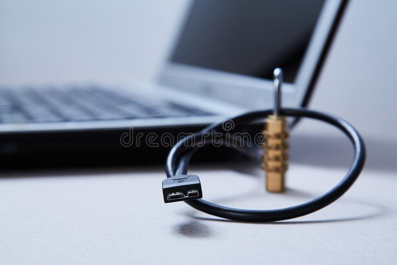 Dator- eller internetsäkerhet Begrepp för dataskydd: usb-kabel, lås och bärbar dator i bakgrunden royaltyfria bilder