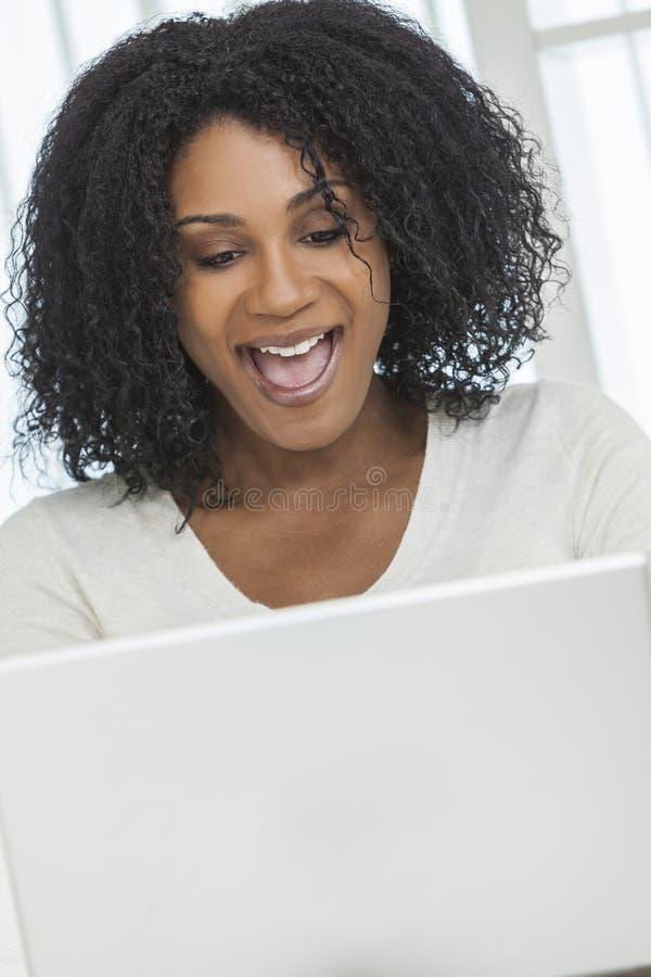 Dator för bärbar dator för överraskning för afrikansk amerikankvinna lycklig royaltyfria foton