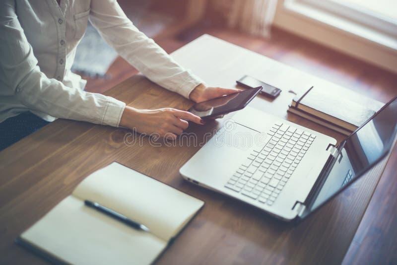 Dator för bärbar dator för hand för affärskvinna funktionsduglig på träskrivbordet royaltyfria foton