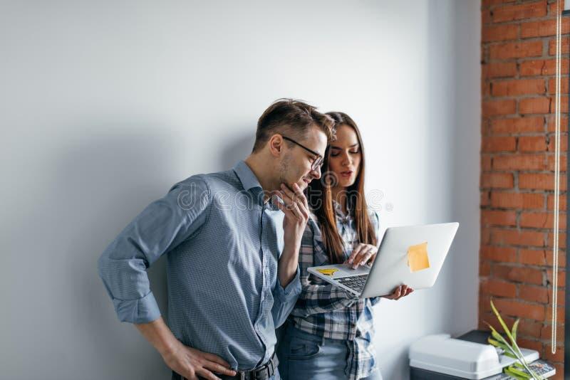 Dator för bärbar dator för lyckliga blandning-lopp par hållande, medan stå och fira över grå väggbakgrund royaltyfria bilder