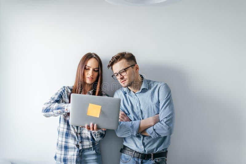 Dator för bärbar dator för lyckliga blandning-lopp par hållande, medan stå och fira som isoleras över grå väggbakgrund royaltyfri bild