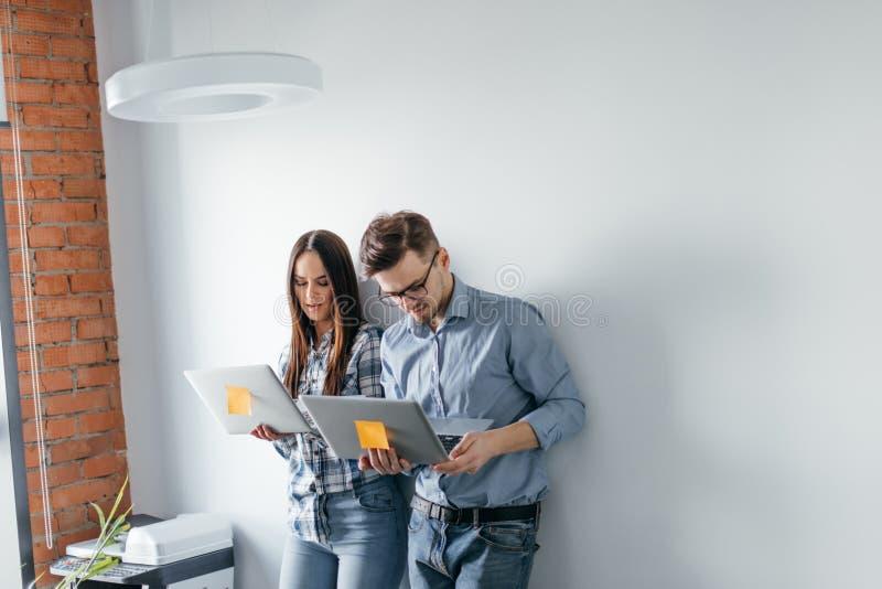 Dator för bärbar dator för lyckliga blandning-lopp par hållande, medan stå och fira som isoleras över grå väggbakgrund arkivbild