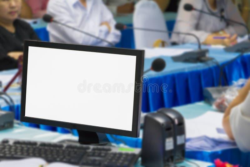 Dator på tabellen och affärsfolket som möter suddighet i rum för konferens för seminariumfinansutbildning royaltyfri foto