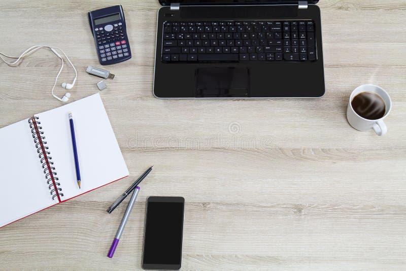 Datorbärbar dator med mobiltelefonen, kontorstillförsel och den varma koppen för svart kaffe med ånga på tappningträskrivbordbakg royaltyfria foton