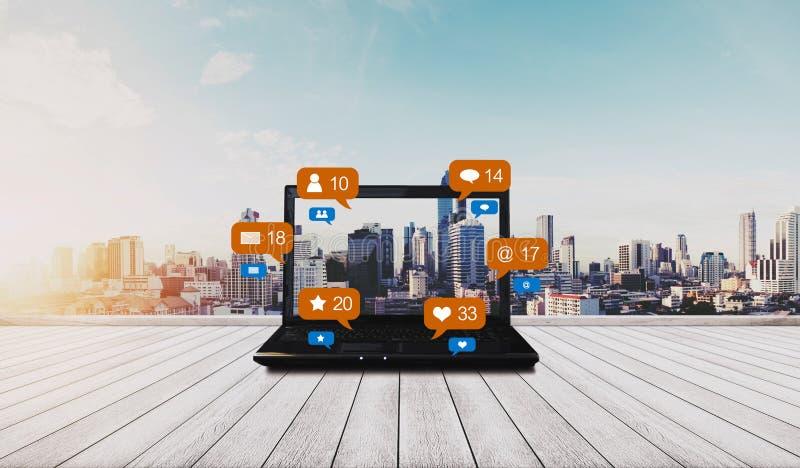 Datorbärbar dator på träskrivbordet och socialt massmedia med sociala nätverksmeddelandesymboler, stadsbakgrund fotografering för bildbyråer