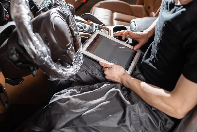 Datordiagnostik av elektroniska system av bilen Bilmekanikern underhåller ett medel med hjälpen av en diagnostik arkivfoton