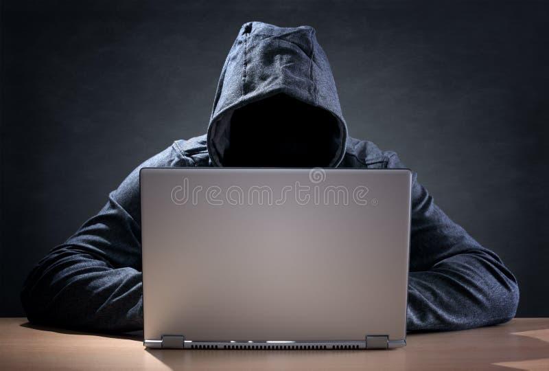 Datoren hacker som stjäler data från en bärbar dator royaltyfri bild