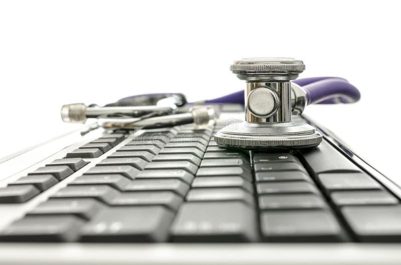 Datoren skrivar med stetoskopet royaltyfri fotografi
