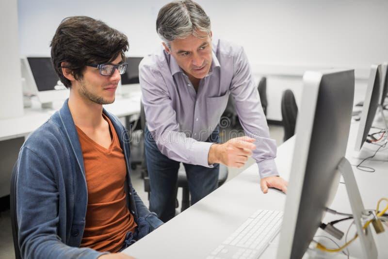 Datorlärare som hjälper en student royaltyfri bild