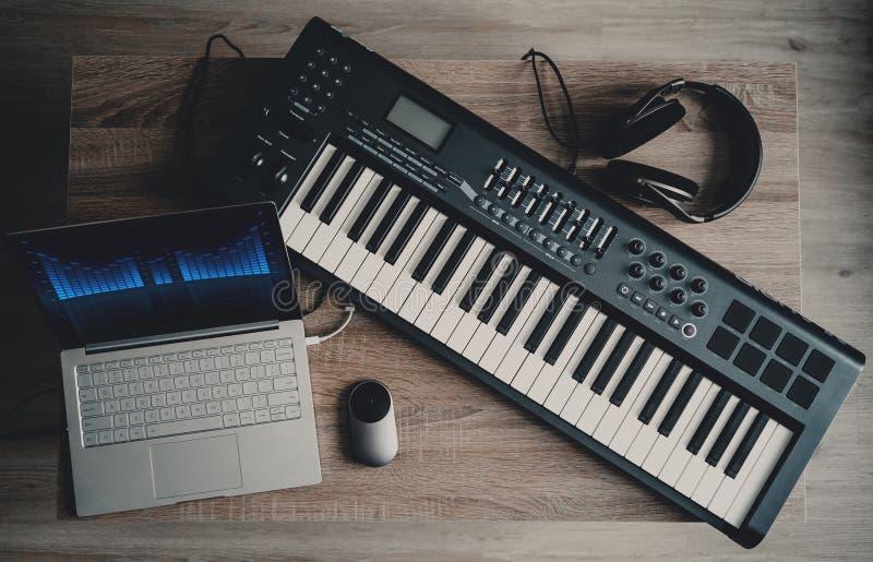 Datormusik, hem- studioutrustning det midi tangentbordet, bärbar datordatoren, headphonen och högtalaren övervakar arkivfoton