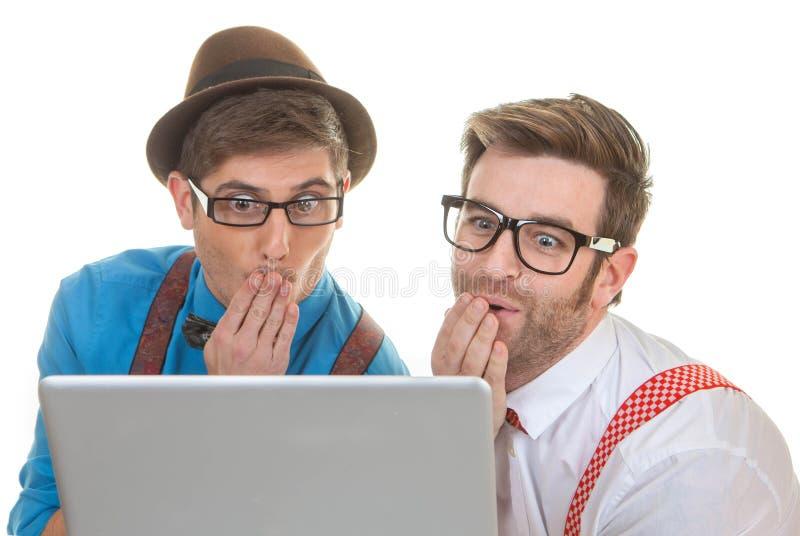 Datornerds som ser bärbara datorn royaltyfria bilder