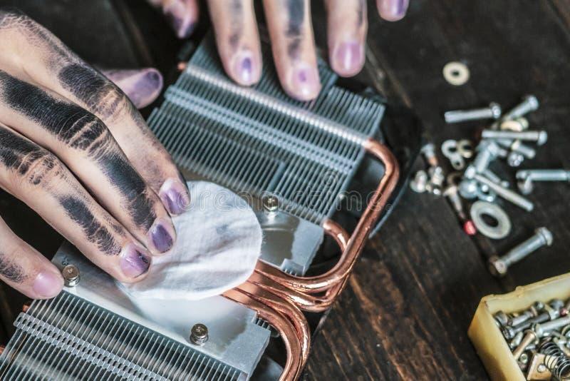 Datorreparationsförlage med mörka smutsiga händer som gör ren det elektroniska stycket på tabellen f royaltyfri foto