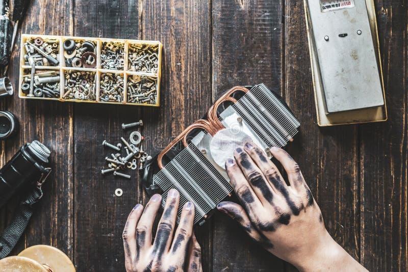 Datorreparationsförlage med mörka smutsiga händer som gör ren det elektroniska stycket på tabellen f royaltyfri bild