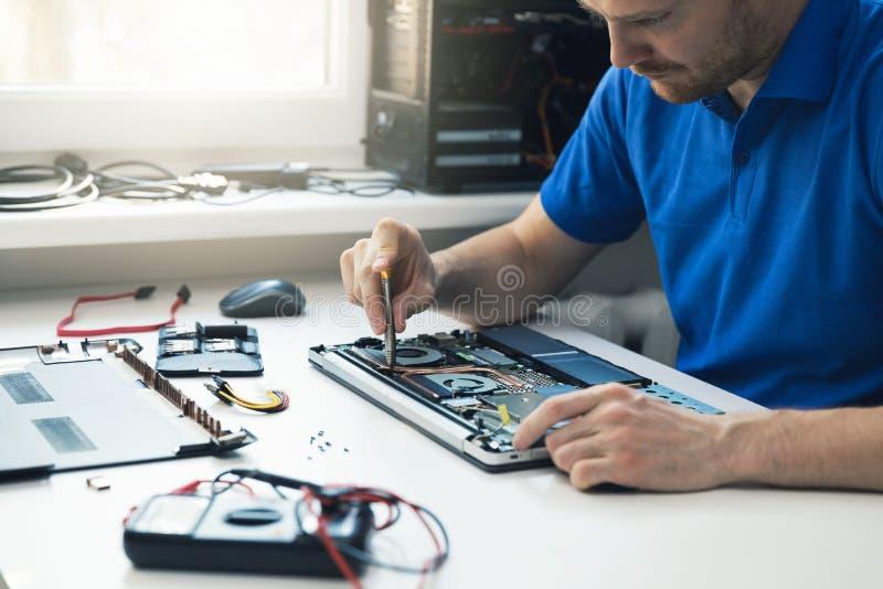 datorreparationsservice - tekniker som reparerar den brutna bärbara datorn royaltyfri fotografi