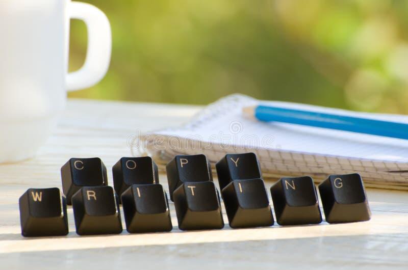 Datortangenter på en vit tabell, ordet Copywriting, anteckningsboken och koppen på grön bakgrund royaltyfri bild