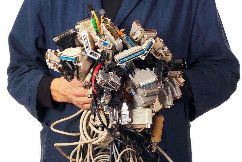 Datorteknikern som rymmer många olika kablar, binder kontaktdon arkivfoto