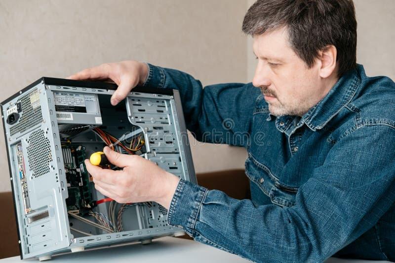 Datorteknikerteknikern med skruvmejsel i hans hand reparerar persondatorn arkivfoton