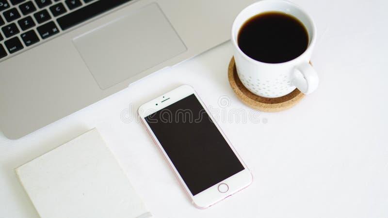 Datortelefon och notepad på den vita bakgrundstabellen royaltyfri foto