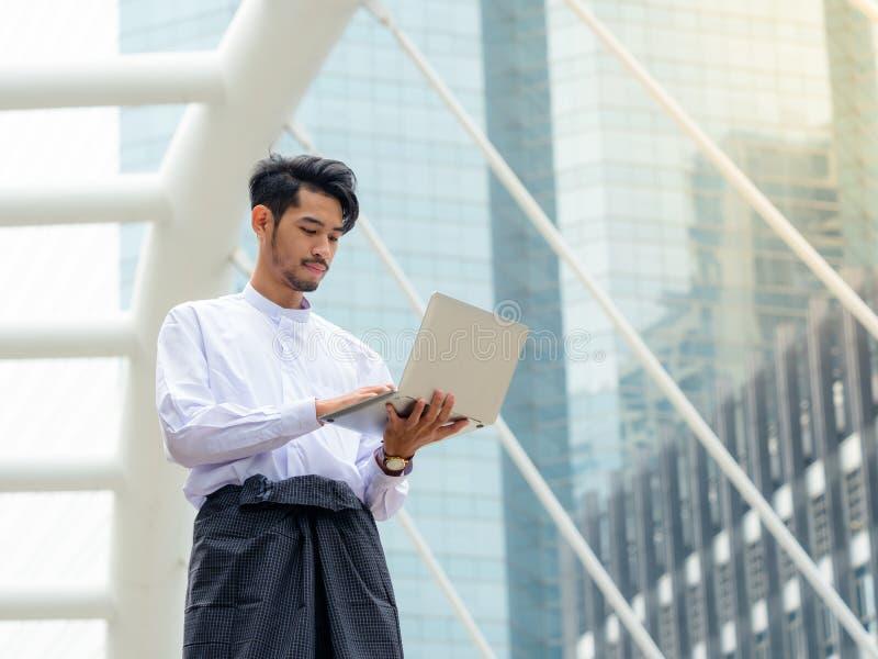 Datos birmanos jovenes del hallazgo del hombre de negocios en el ordenador portátil, It& x27; tiempo de s para hablar fotografía de archivo