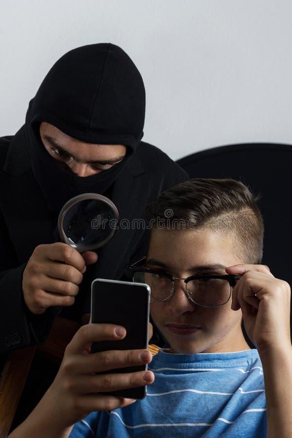 Datos de espionaje enmascarados del hombre del smartphone de adolescente foto de archivo libre de regalías