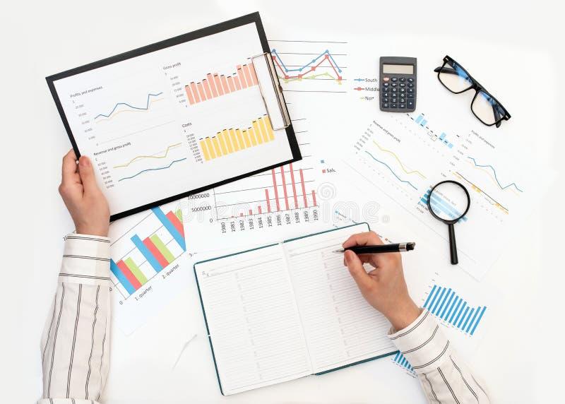 Datos de registro de las manos de una mujer de un informe con los gráficos foto de archivo libre de regalías