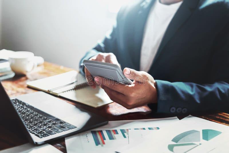 datos de trabajo del control del hombre de negocios de las finanzas del documento en oficina usando la calculadora para calcular fotografía de archivo libre de regalías