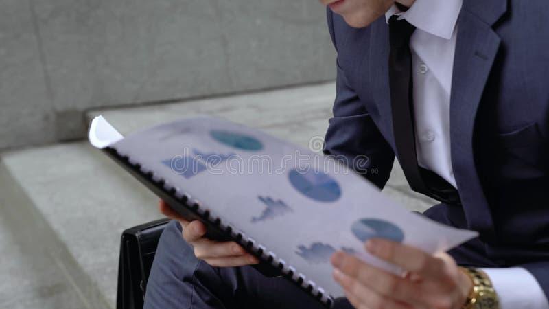 Datos expertos financieros de la lectura sobre las rentas y las deudas, amenaza de la compañía de la quiebra fotos de archivo libres de regalías