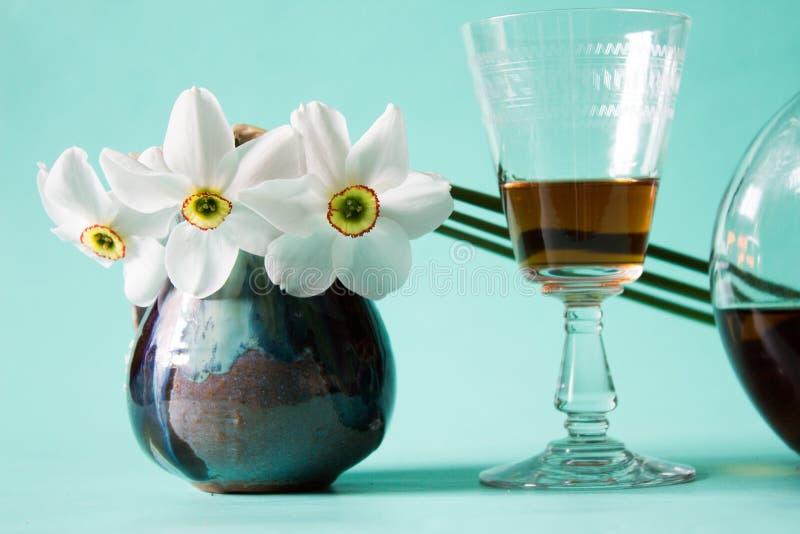 Datte romantique Cognac ou eau-de-vie fine Jonquilles blanches dans le vase à vintage photo libre de droits