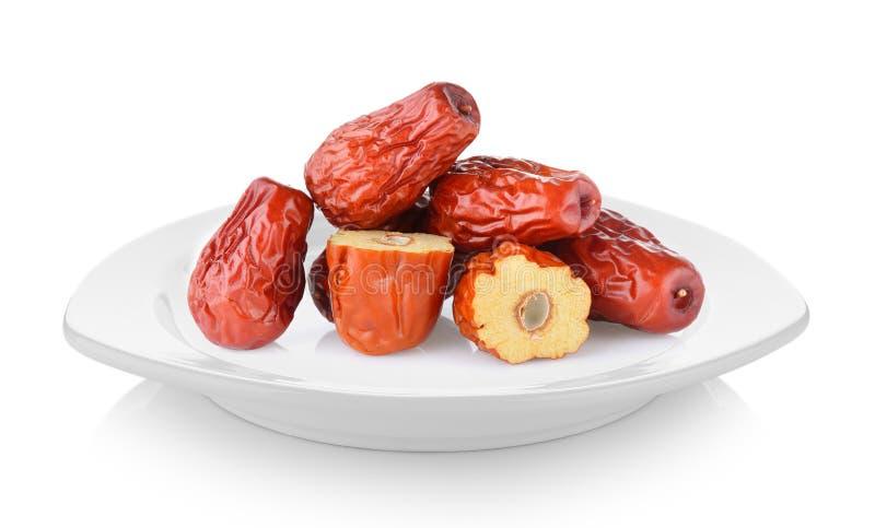 Dattero o giuggiola rosso secco di cinese in piatto bianco sul backgro bianco fotografie stock