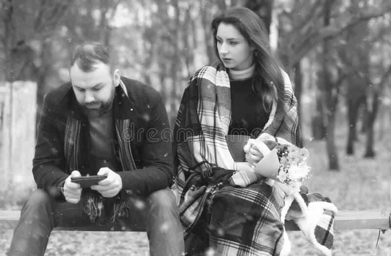 Datuje w parkowych kochanków na ławce w śniegu fotografia stock