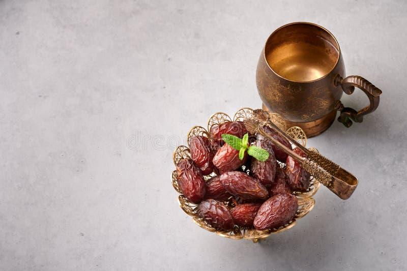 Datum Fruits of Kurma in de bronzen plaat bij grijze betonnen achtergrond Data en water zijn Ramadan Iftar-maaltijd stock foto