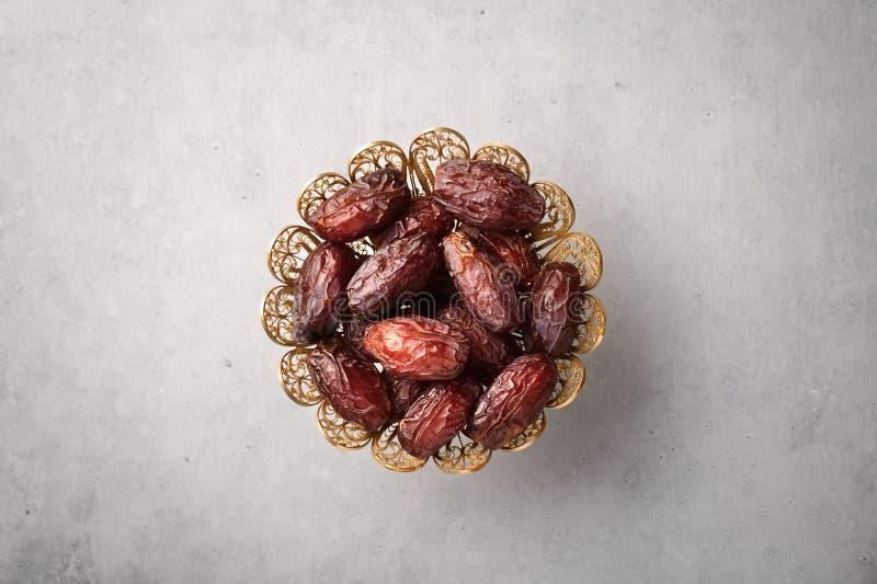 Datum Fruits of Kurma in de bronzen plaat op grijze betonnen achtergrond Dates is Ramadan food Ramazan Iftar food stock fotografie