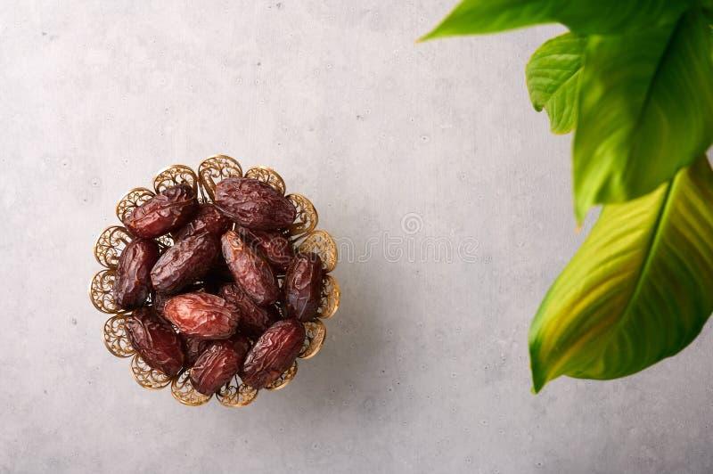 Datum Fruits of Kurma in de bronzen plaat op grijze betonnen achtergrond Dates is Ramadan food Ramazan Iftar food royalty-vrije stock foto's